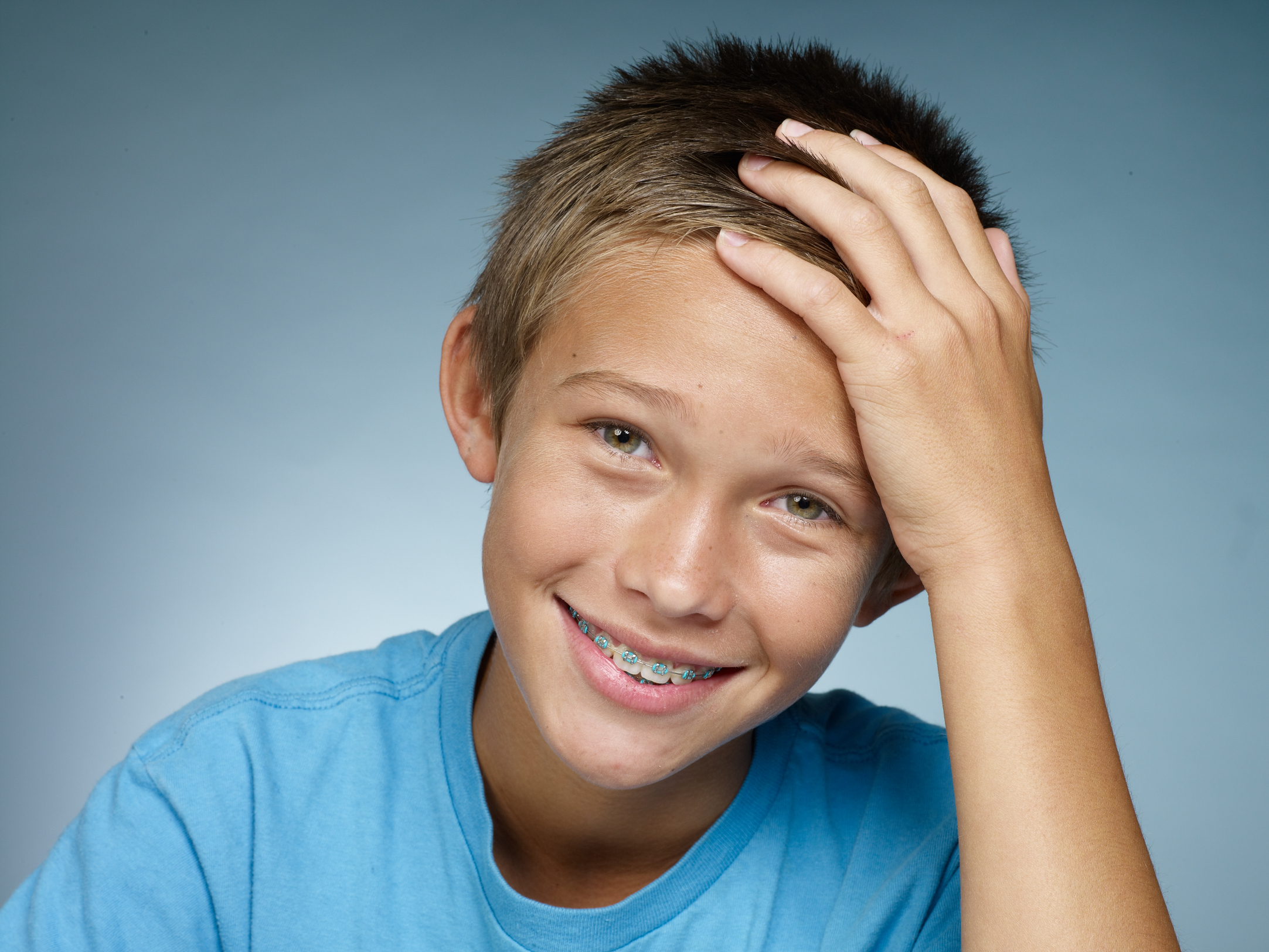 Boy with Braces holding head